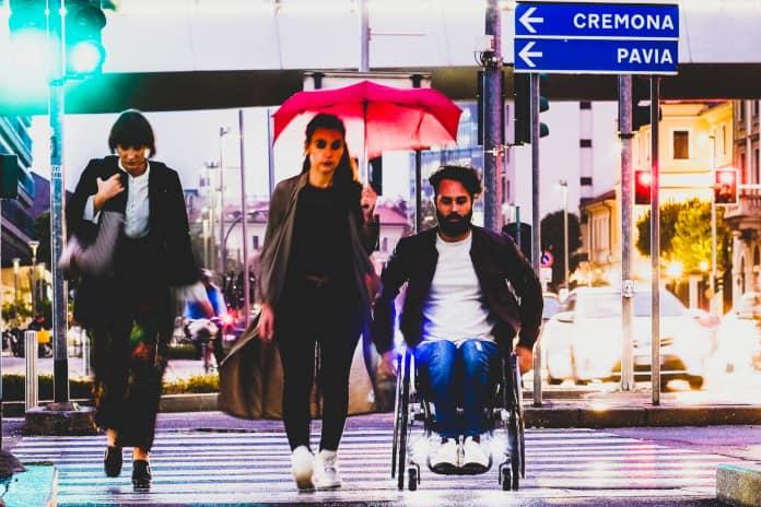 Personen überqueren Straße, eine im Rollstuhl